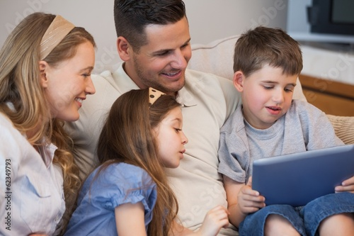 Happy family of four using digital tablet in living room