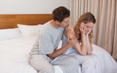 Man consoling a sad woman in bedroom