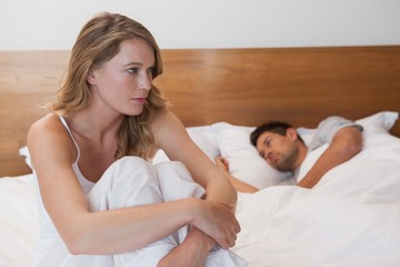Sad woman with man sleeping in background