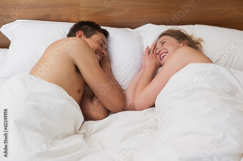 Happy relaxed young couple in bed