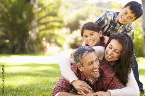 Family Lying On Grass In Countryside - 62349916