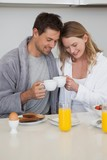 Young couple with coffee cups in kitchen