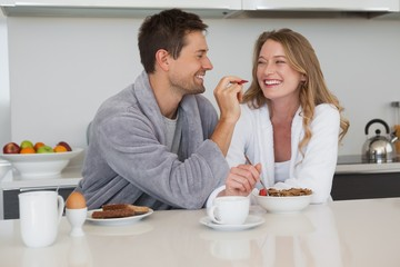 Young man feeding woman a fruit in kitchen