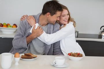 Loving woman embracing man at breakfast table