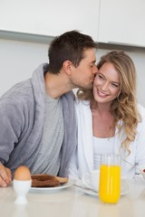Man kissing happy woman at breakfast table