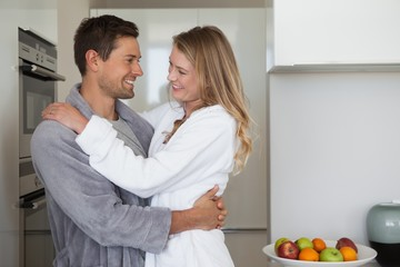 Side view of a loving young couple in kitchen