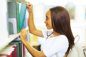 female african college student pulling a library book