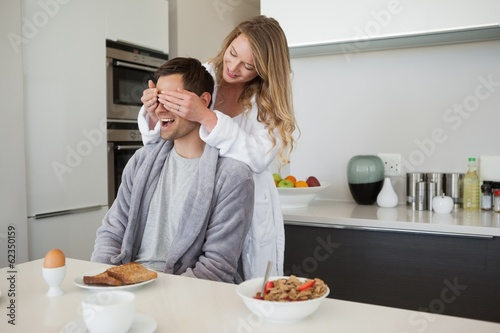 Young woman covering mans eyes in kitchen