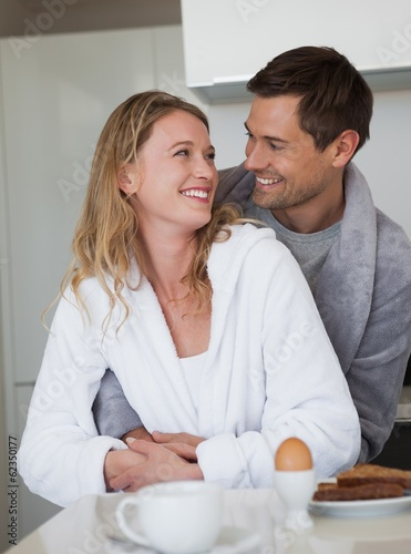 Loving young couple looking at each other in kitchen
