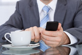 Businessperson Using Cellphone With Coffee Cup Placed At Desk