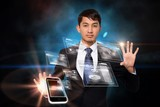 Serious businessman touching interface with smartphone