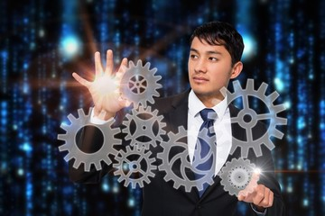 Asian businessman touching cogs and wheels