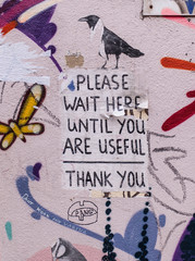 """Note on a wall saying """"Please wait here until you are useful"""""""