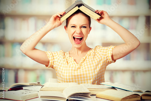 wild girl student with glasses shouts with books