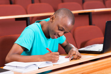 male african college student writting classwork