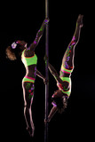 Strong slender girls dancing on pylon