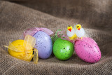 Easter eggs and decorative chickens on burlap
