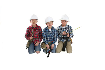 Three young boys in construction  hardhats playing