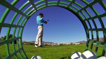 Golfer Hits Tee Shot At Driving Range