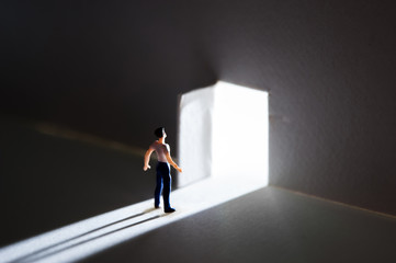 開いた扉から光を受ける男性