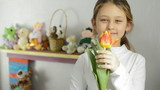 Positive little girl smelling a tulip