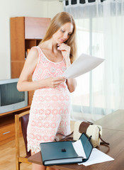pregnant woman reading paper document