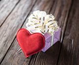Gift box and heart on old wooden background