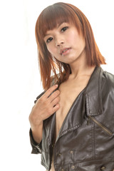 Beautiful young Chinese woman wearing leather jacket and denim s