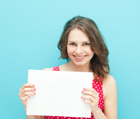 beautiful girl with a white sheet of paper on a blue background