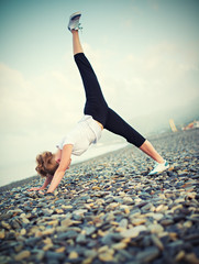 woman in white doing yoga and sport exercises on  beach