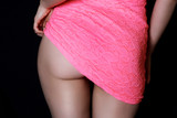 woman ass  in fitting sexy pink dress. black background