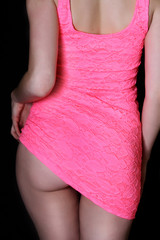 young sexy woman back in short pink dress and showing buttocks