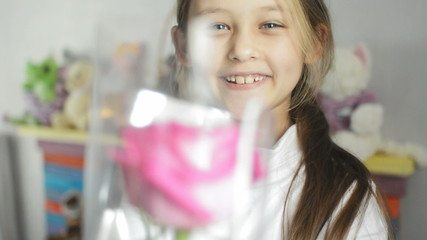 little girl gives a red rose, close-up