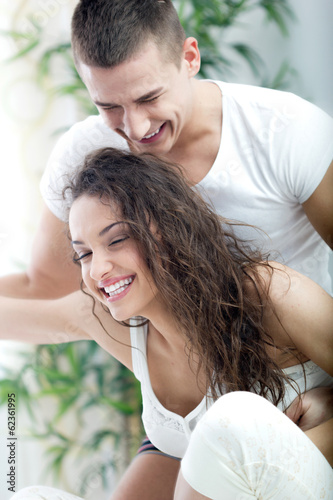 Young happy couple in love tickles