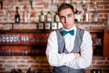 portrait of young bartender in bar or nightclub