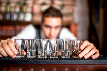bartender preparing and lining shot glasses for alcoholic drinks