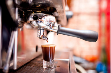Espresso machine making special strong coffee in shot glass