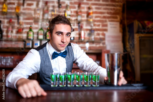 portrait of young male barman behind the bar with alcoholic shot