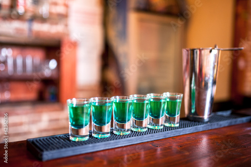 Blue alcoholic liquid in shot glasses standing on the counter