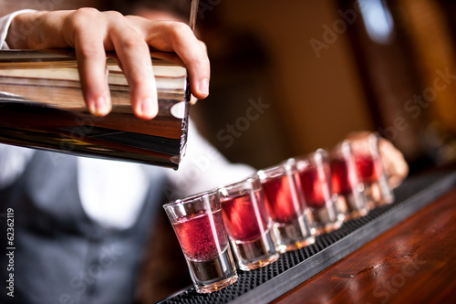 close-up of barman hand pouring alcohol into shot glasses