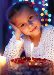 Cute little girl looking at cake with a candle