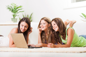 Three cheerful Friends with laptop