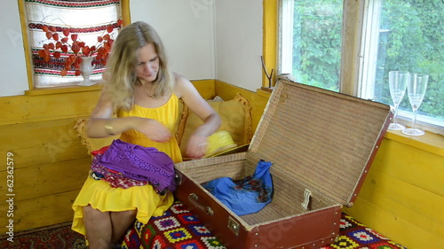 girl with dress sitting on bed on knees clothe put into suitcase