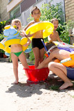 four little children splashing and having fun in their yard