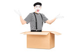 Male mime artist sitting in carton box, gesturing with hands