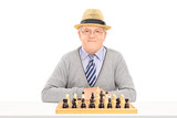 Male pensioner posing behind a chessboard
