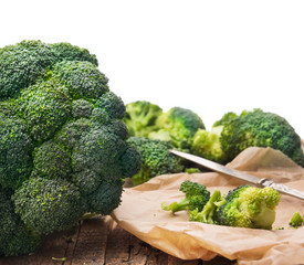 broccoli head on  table in crumpled paper with knife,isolated