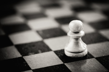 White chess pawn standing on chessboard