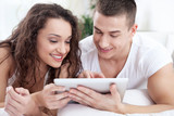 Young couple sitting on the bed using tablet pc