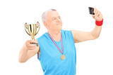Senior athlete taking selfie with trophy in his hand